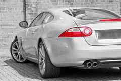 Luxury sports car. Photo of a jaguar xk luxury sports car in monochromatic tone showing red tail lights Royalty Free Stock Photography