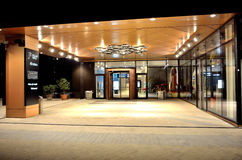 Luxury store entrance by night. Modern architecture of the luxury mall entry illuminated by lights in night Royalty Free Stock Images