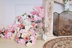 Luxury stylish interior of apartment. White walls decorated by flowers stock images