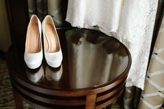 Luxury stylish white wedding shoes on wooden table with a dress in background Royalty Free Stock Photos
