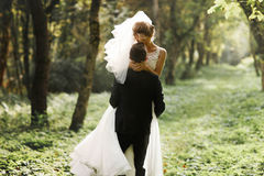 Luxury stylish young bride and groom on the background spring s. Unny green forest stock photography