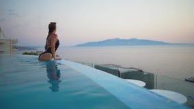 Luxury summer vacation - Woman swimming underwater in bikini in infinity pool at travel hotel resort. Elegant lady stock video footage