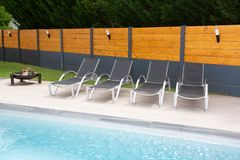 Luxury Swimming Pool and bathe chair blue water in summer against grey wood wall. A Luxury Swimming Pool and bathe chair blue water in summer against grey wood royalty free stock photos