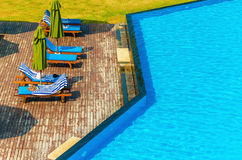 Luxury swimming pool with blue sun loungers Royalty Free Stock Image