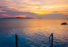 Luxury swimming pool in front of sea at during sunset Royalty Free Stock Photos