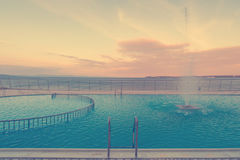 Luxury swimming pool in front of sea at during sunset Royalty Free Stock Image