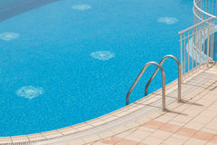 Luxury swimming pool with grab bars ladder Royalty Free Stock Photography