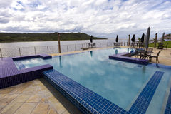 Luxury swimming pool beside lagoon Royalty Free Stock Photo
