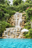 Luxury swimming pool nearby tropical forest and waterfall Royalty Free Stock Photography
