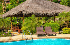Luxury swimming pool with rattandeck chairs Stock Photos