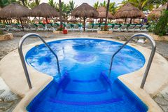 Luxury swimming pool scenery in Mexico. PLAYA DEL CARMEN, MEXICO - JULY 12, 2011: Luxury swimming pool scenery at RIU Yucatan Hotel in Playa del Carmen, Mexico Stock Photo