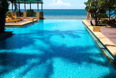 Luxury swimming pool in tropical resort with blue sky and ocen Stock Photos