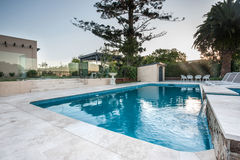Luxury swimming pool view from a corner with trees Royalty Free Stock Images