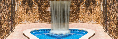 Luxury swimming pool with waterfall. In the background a mediterranean wall decorated with sandstones Royalty Free Stock Photo
