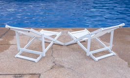 Luxury swimming pool with white deckchairs Stock Photo