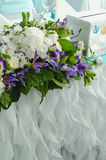 Luxury table beautiful, rich decoration with lush leaves, white hydrangea, delicate cream roses, purple eustoma, blue Stock Photos