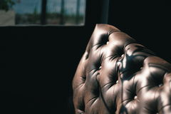Luxury texture of leather furniture on Dark Background. With light and shadow near the window in the afternoon Royalty Free Stock Images