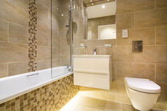 Luxury three piece bathroom in beige - brown royalty free stock photos