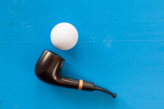 Luxury tobacco pipe and golf ball on the blue table Royalty Free Stock Photo