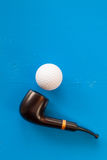 Luxury tobacco pipe and golf ball on the blue table Royalty Free Stock Images