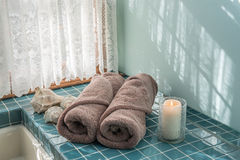 Luxury Towels in Master Bath. Luxury master bath escape with spa towels, lit candle, and large sea shells stock image