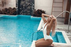 Luxury travel bikini blonde girl with sexy body in white swimwear posing by swimming pool at luxurious villa. Fashion colors,. Glamour Portrait of beautiful stock photos