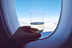 Luxury travel lifestyle on board the airplane. Hand holding up a glass of white wine in front of airplane window with a view of the blue sky and clouds royalty free stock images