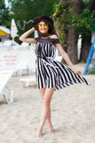 Luxury travel woman in black and white beachwear walking taking a stroll on sand summer beach. Girl tourist on summer Royalty Free Stock Photography