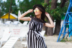 Luxury travel woman in black and white beachwear walking taking a stroll on sand summer beach. Girl tourist on summer Royalty Free Stock Photos