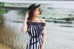 Luxury travel woman in black and white beachwear walking taking a stroll on sand summer beach. Girl tourist on summer Stock Photo
