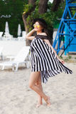 Luxury travel woman in black and white beachwear walking taking a stroll on sand summer beach. Girl tourist on summer Royalty Free Stock Images