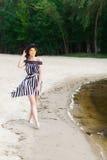 Luxury travel woman in black and white beachwear walking taking a stroll on sand summer beach. Girl tourist on summer Stock Image