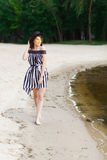 Luxury travel woman in black and white beachwear walking taking a stroll on sand summer beach. Girl tourist on summer Stock Photos