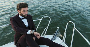 Luxury traveling and working. Stylish businessman on a yacht or boat against a sea. He is pleased with the success in. Businessman on a yacht or boat against a stock video footage