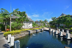 Luxury upscale resort hotel with water flowing into pond surrounded by bungalows. In clear blue sky. Suitable settings for honeymoon, wedding, vacation and stock photos