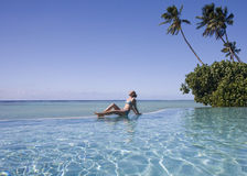 Luxury Vacation - Cook Islands - South Pacific. Young woman sunbathing at a luxury resort on Aitutaki Lagoon in the Cook Islands in the South Pacific stock images