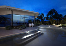 Luxury villa at night with an illuminated pool. Luxury modern villa or house with large plate glass windows at night with an illuminated curving swimming pool Royalty Free Stock Images