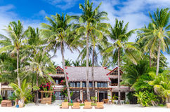 Luxury villa and palm trees at beautiful white sandy beach Royalty Free Stock Images