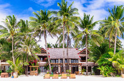 Luxury villa and palm trees at beautiful white sandy beach Stock Images