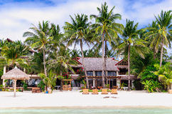 Luxury villa and palm trees around at beautiful white sandy beach Stock Images