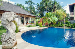 Luxury villa with pool outdoor. Exterior luxury villa in Bali with a garden and fish fountain in the swimming pool outdoors royalty free stock photography