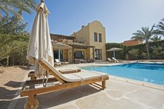 Swimming pool at a luxury tropical holiday villa. Luxury villa show home at tropical summer holiday resort with swimming pool and sun chairs in garden Stock Photography