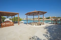 Swimming pool at at luxury tropical holiday villa resort. Luxury villa show home in tropical summer holiday resort with swimming pool and sun chairs Royalty Free Stock Images