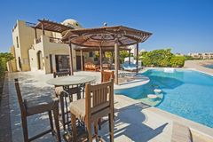 Swimming pool at at luxury tropical holiday villa resort. Luxury villa show home in tropical summer holiday resort with swimming pool and sun chairs Stock Photo