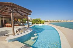 Swimming pool at at luxury tropical holiday villa resort. Luxury villa show home in tropical summer holiday resort with swimming pool and sun chairs Royalty Free Stock Image