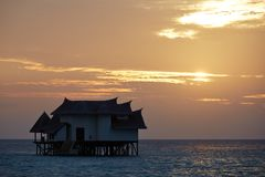Luxury Villa, Vittaveli Island, Maldives. Thatched roof villa in the sea, cloudy sunset stock photo