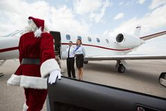 Luxury VIP santa with Private Jet. Santa disembarking car while walking towards private jet with pilot and airhostess standing by Stock Photography