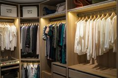 Luxury walk in closet / dressing room with lighting. And jewel display. Dresses, handbags, blouses and sweaters on hangers in the wardrobes. Hoizontal royalty free stock images