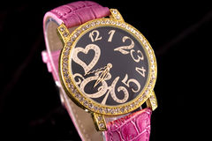 Luxury Watch. Woman luxury watch in golden tone with crystals and ping strap royalty free stock photography
