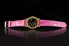 Luxury Watch. Woman luxury watch in golden tone with crystals and ping strap stock photo